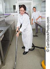 restaurant staff cleaning kitchen floor