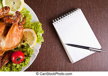 Restaurant table with roast chicken, notebook and pen
