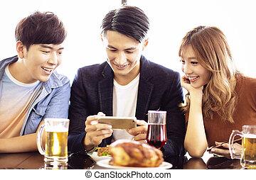 restaurante, smartphone, amigos, jovem, observar