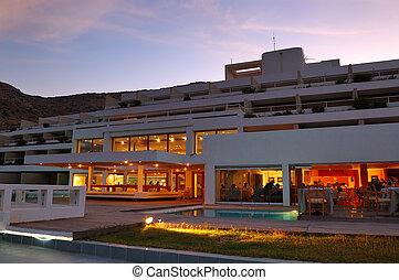 Restaurant's illumination of luxury hotel during sunset, Crete, Greece