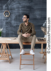 Restful businessman in casualwear sitting on wooden table with his feet on chair