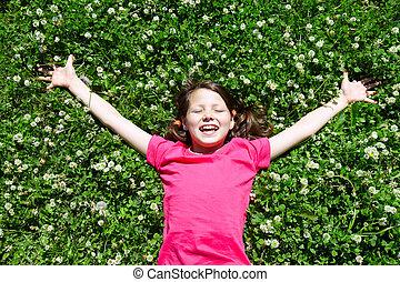 Restful child - Portrait of a joyful little girl lying on ...
