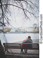 Image of affectionate young couple sitting on the bench in park
