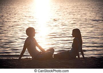 Photo of serene couple sitting on the seashore and talking at sunset