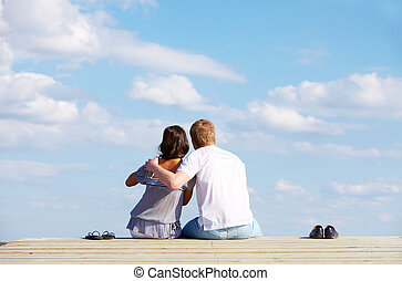 Image of guy embracing his girlfriend while enjoying hot summer day
