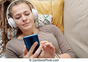 Restful girl listening to music in headphones and scrolling in smartphone