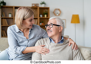 Restful senior man and his young daughter relaxing on couch and talking at home