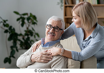 Restful senior man on couch holding hand of his young blonde daughter