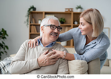 Restful senior man on couch looking at his young daughter standing near by