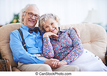 Elegant seniors in smart clothes sitting on sofa and looking at camera