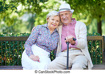 Restful seniors - Happy seniors sitting on bench in the park...