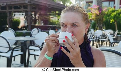 Resting blond woman drinking a cup of coffee in a modern cafeteria in slo-mo