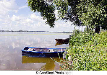 Boats resting on the lake coast with nice view of lake.