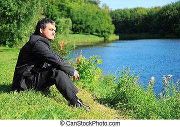 resting businessman sitting on river bank