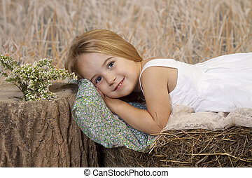 Beautiful And Sexy Country Girl Sitting On A Bale Of Hay