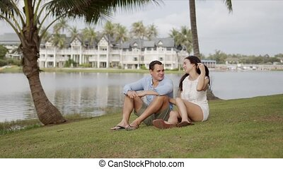 Resting couple enjoying in journey while sitting on lawn at ...