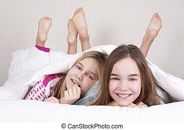 resting - couple smiling girls between the bedclothes