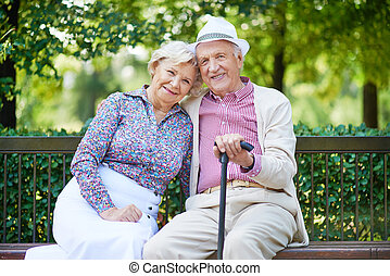 Resting in park - Happy seniors sitting on bench in the park...