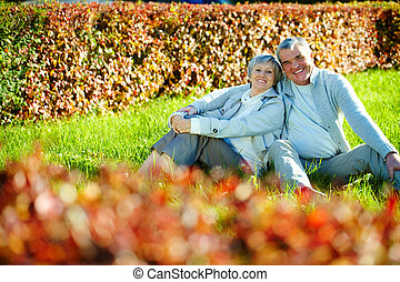 Resting on lawn - Photo of happy aged man and woman looking...