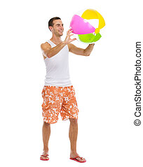 Resting on vacation happy young man playing with beach ball