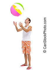 Resting on vacation happy young man throwing beach ball up