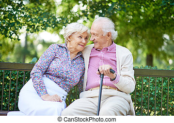 Resting outdoors - Happy senior couple sitting on bench in...