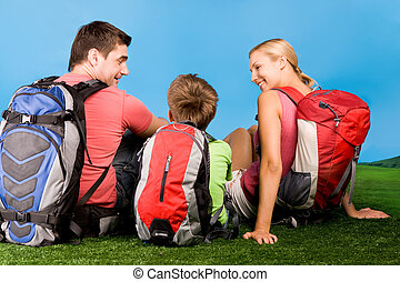 Resting - Rear view of family chatting on grassland during ...