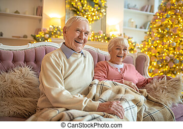 Senior couple sitting in a beautiful room and feeling convenient