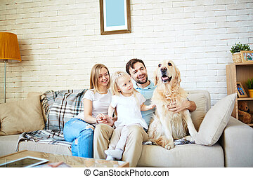 Resting together - Cute little girl and her parents with dog...