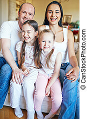 Joyful family of four looking at camera during home rest