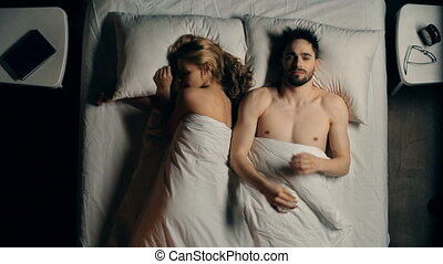 Right from above view of man wide awake at night lying with his partner sleeping soundly