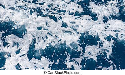 Restless, splashing foamy blue sea water from above