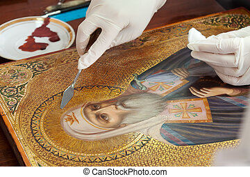 restoration of old gilded icon with filling knife at...