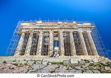 Restoration work in progress at world heritage ancient Parthenon with machine crane, scaffolding and blue sky background, Athens, Greece