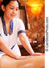 Restoring life balance. Confident Thai massage therapist massaging female back and smiling