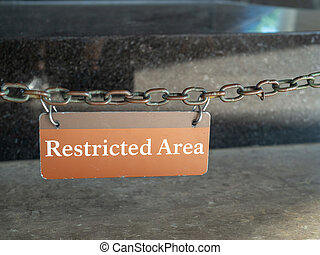 Restricted area sign hanging in front of a protected area - ...