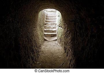 Dark stone room with a stairway encased in sunlight.