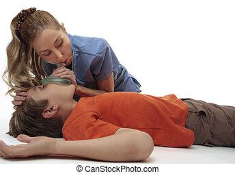 Resuscitating unconscious boy - Female nurse using a ...