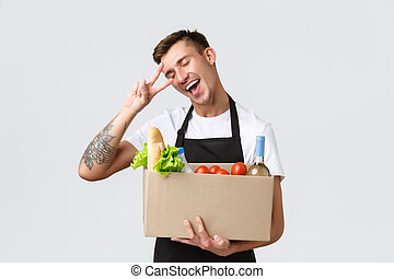 Retail, grocery shopping and delivery concept. Charismatic handsome salesman, courier in black apron show peace sign and holding box with groceries, prepare clients order for courier company