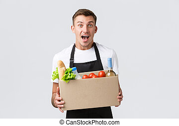 Retail, grocery shopping and delivery concept. Excited salesman announce awesome promo, holding box with groceries food, processing order, delivering food to customer, white background