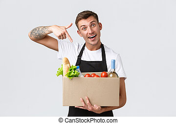 Retail, grocery shopping and delivery concept. Handsome courier in black apron handing over box with groceries, salesman prepared package, pointing at box with food groceries, white background
