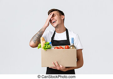 Retail, grocery shopping and delivery concept. Silly cheerful salesman in store packing order for couriers, holding box with food, selling groceries, laughing and smiling upbeat, white background
