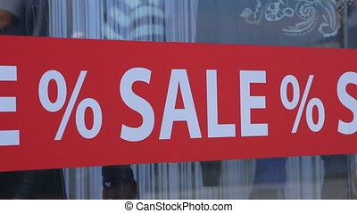 Advertising red retail shop window sticker % SALE %, pedestrians are reflected in the glass, closeup Canon C100