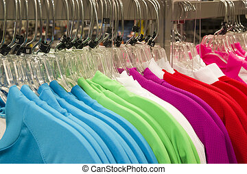 Multiple colors of sprts shirts hang on the rack