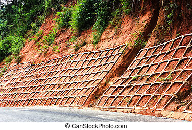 retaining wall protects mountain road from landslides