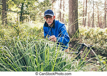 Retired active man standing with bicycle observing bushes.