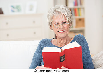 Retired amused woman reading an interesting book