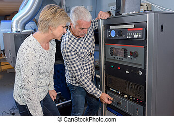 retired couple checking up home thermal boiler together