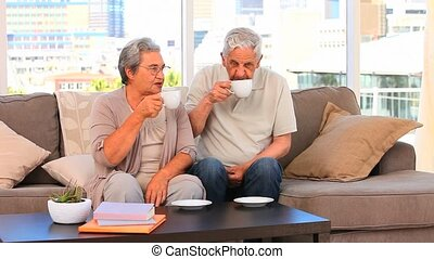 Retired couple drinking a cup of te