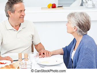 Retired couple eating  in the kitch